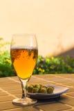 橄榄开胃菜啤酒陪同的杯对树荫 免版税库存照片