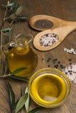 橄榄油、两把匙子有盐的和胡椒在一张木桌上 免版税图库摄影