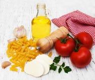 橄榄油、无盐干酪乳酪、fusilli面团、大蒜和蕃茄 库存照片