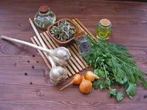 橄榄油和向日葵种油用绿叶莳萝和荷兰芹,杜松子,葱,在一张木桌上的干燥空间 免版税库存图片