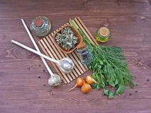 橄榄油平的看法用绿叶莳萝和荷兰芹,杜松子,葱,在一张木桌上的干燥空间 免版税库存照片