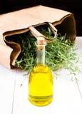 橄榄油瓶和草本与纸袋在白色木backg 免版税库存图片