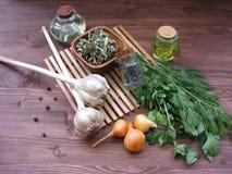 橄榄油用绿叶莳萝和荷兰芹,杜松子,葱,在一张木桌上的干燥空间 免版税库存图片