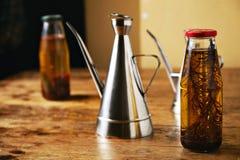 橄榄油用草本和钢分配器 免版税库存照片