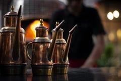 橄榄油铜调味瓶传统分配器细节在意大利餐厅 免版税库存图片