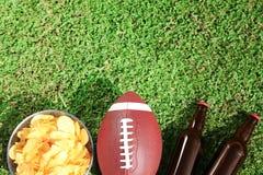 橄榄球、饮料和芯片的球在新鲜的绿色领域草,平的位置 免版税库存图片