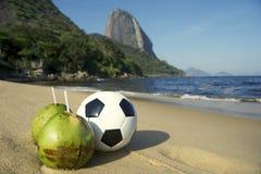 橄榄球与新鲜的椰子里约海滩的足球 库存图片