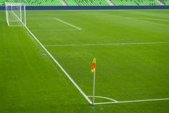 橄榄球与白色标记、绿草纹理和角落旗子的足球场 免版税库存照片