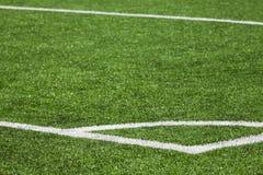 橄榄球与绿草的运动场背景 图库摄影