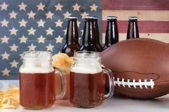 橄榄球加上啤酒和芯片与美国旗子在backgroun 库存图片