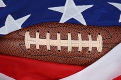 橄榄球和旗子 库存照片