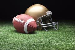 橄榄球和盔甲在草反对黑暗的背景 库存照片