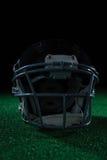 橄榄球在人为草皮的头齿轮 图库摄影