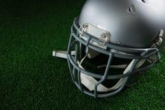 橄榄球在人为草皮的头齿轮 免版税图库摄影