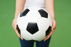 橄榄球在妇女的手上 图库摄影