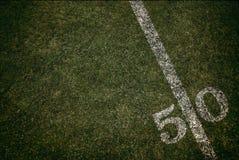 橄榄球场研了五十调车场界线 星期五晚上光 库存照片