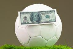 橄榄球坐与美金的草表面胶合了对它,打赌概念 图库摄影