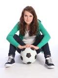 橄榄球女孩球员坐少年的足球 库存图片