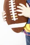 橄榄球孩子的球玩具在男孩手上有白色背景 免版税库存照片