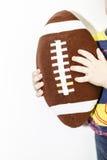 橄榄球孩子的球玩具在男孩手上有白色背景 免版税图库摄影