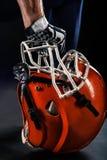 橄榄球拿着盔甲的运动员球员 免版税库存图片