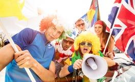橄榄球支持者扇动欢呼在足球杯子比赛以后的朋友 免版税库存照片