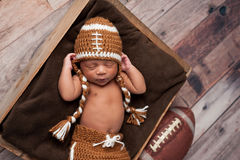 橄榄球服装的新出生的男婴 库存照片
