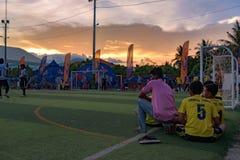 橄榄球比赛的结尾,放松在草地的柬埔寨球员 免版税库存照片