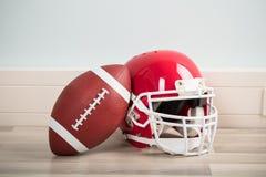 橄榄球球和盔甲 库存图片