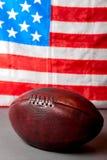 橄榄球球和老荣耀旗子 库存照片