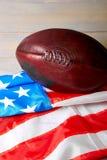 橄榄球球和老荣耀旗子 库存图片
