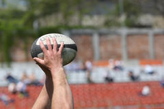 橄榄球球在手上 免版税图库摄影