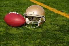 橄榄球盔和球在球门线附近 免版税库存图片