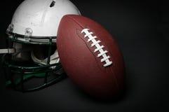 橄榄球盔和球 免版税库存图片