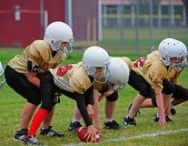 橄榄球线路准备好的并列争球青年时&# 图库摄影