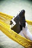 橄榄球装楔放松在海滩吊床的足球运动员 库存图片