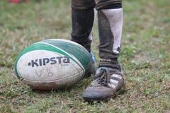 橄榄球要素在8年以下: 鞋子和球 免版税库存照片