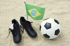 橄榄球解雇在沙子的巴西旗子足球 库存照片