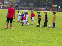 橄榄球训练的小孩在公园 图库摄影