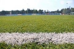 橄榄球足球运动场的特写镜头综合性草 免版税库存照片