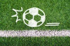 橄榄球辗压在足球场草的手图画 库存照片