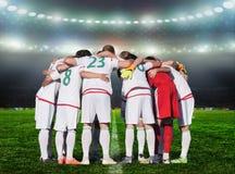 橄榄球队球员拥抱脖子,并且为在使用前祈祷 图库摄影