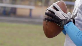 橄榄球 拿着一个球用在慢动作的两只他的手的坚定的美国橄榄球运动员 特写镜头  股票录像