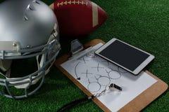 橄榄球头齿轮、片剂、口哨和橄榄球在人为草皮 库存图片