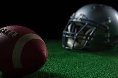 橄榄球头齿轮和橄榄球在人为草皮 库存图片