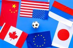 橄榄球championat 美国,加拿大,欧洲,日语,中国、俄国旗子和橄榄球球在蓝色背景 免版税库存图片