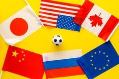 橄榄球championat 美国,加拿大,欧洲,日语,中国、俄国旗子和橄榄球球在黄色背景 库存图片