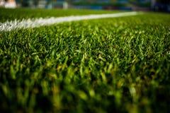 橄榄球stafium,关闭绿色明亮的五颜六色的草沥青与美好的bokeh 库存照片