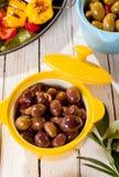 橄榄盘在木表上的与开胃小菜 免版税库存照片