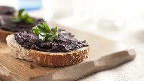 橄榄色的橄榄凤尾鱼汤用在面包片的新鲜的荷兰芹 库存图片